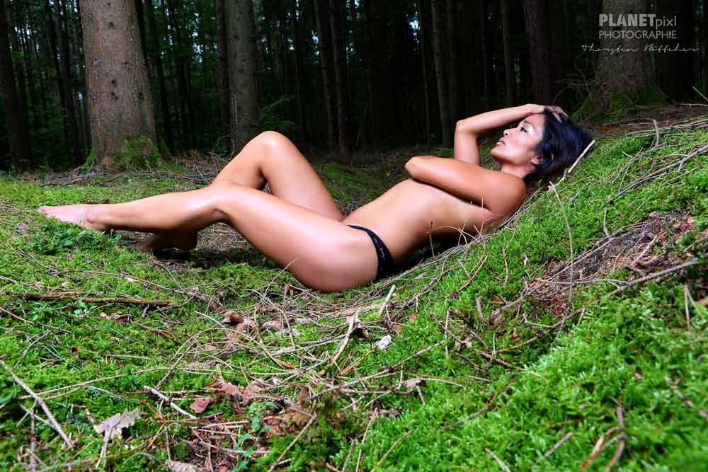 Aktmodel weiblich im Wald liegend