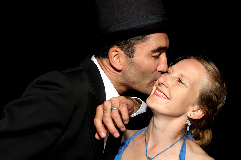 Bräutigam mit Hut küsst Braut