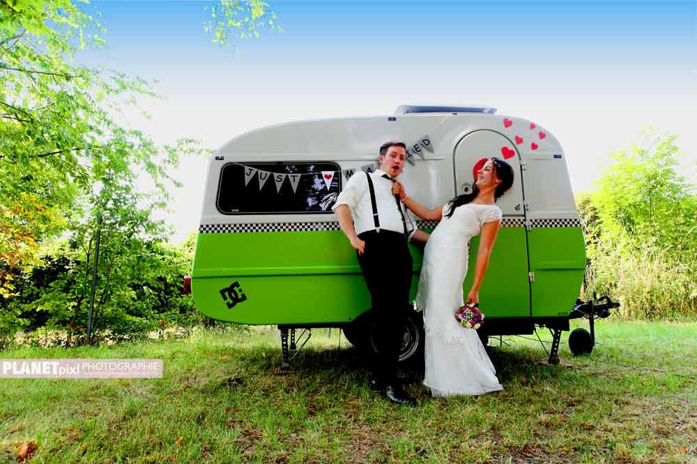Brautpaar vor altem Wohnanhänger