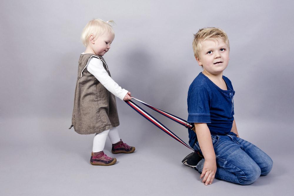 Kleine Schwester zieht Bruder an den Hosenträgern