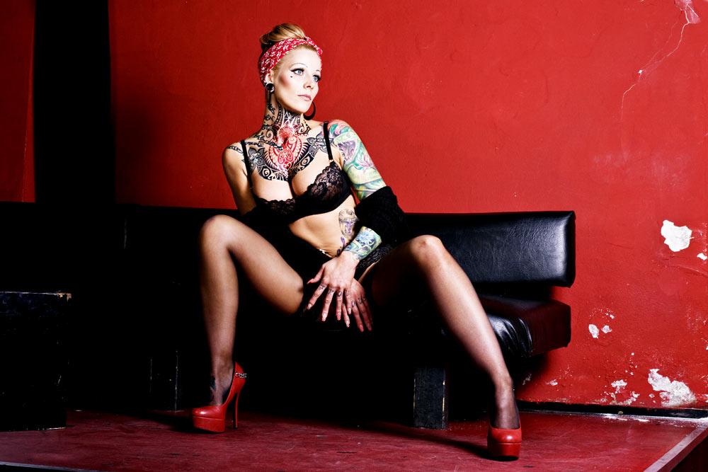 Frau mit Tätowierungen auf schwarzem Ledersofa sitzend
