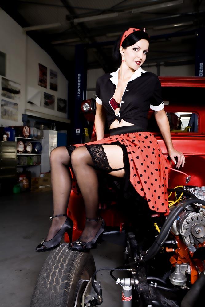 Pin-up-girl sitzend auf Hotrod
