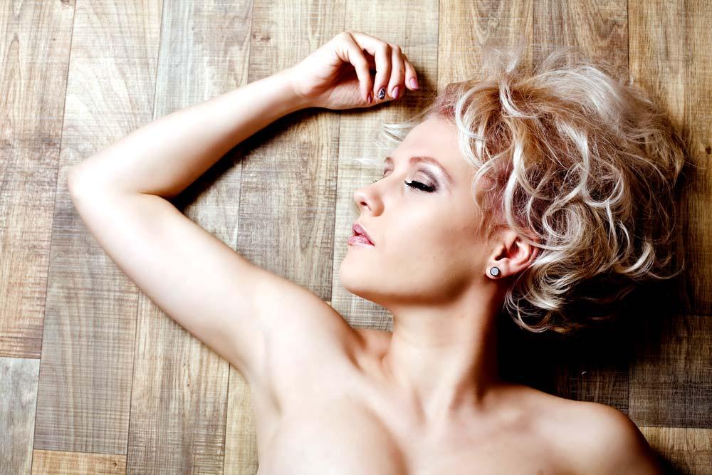 Portrait blonde Frau auf dem Boden liegend