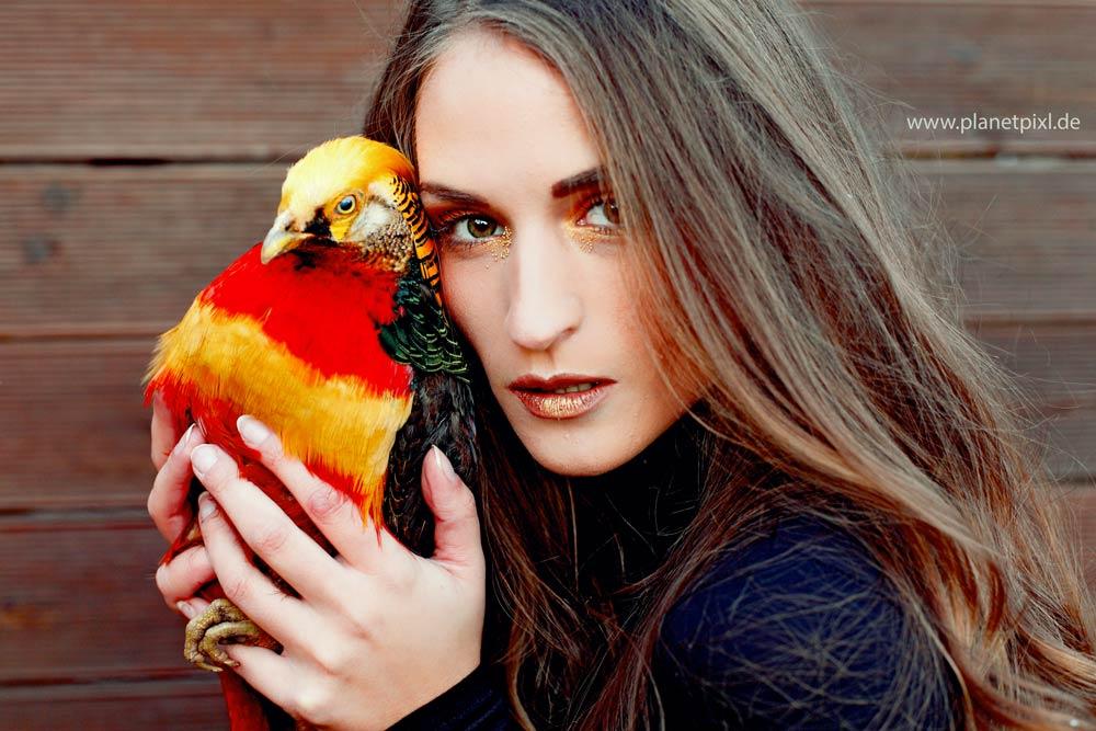 Portrait Frau mit Vogel in den Händen haltend