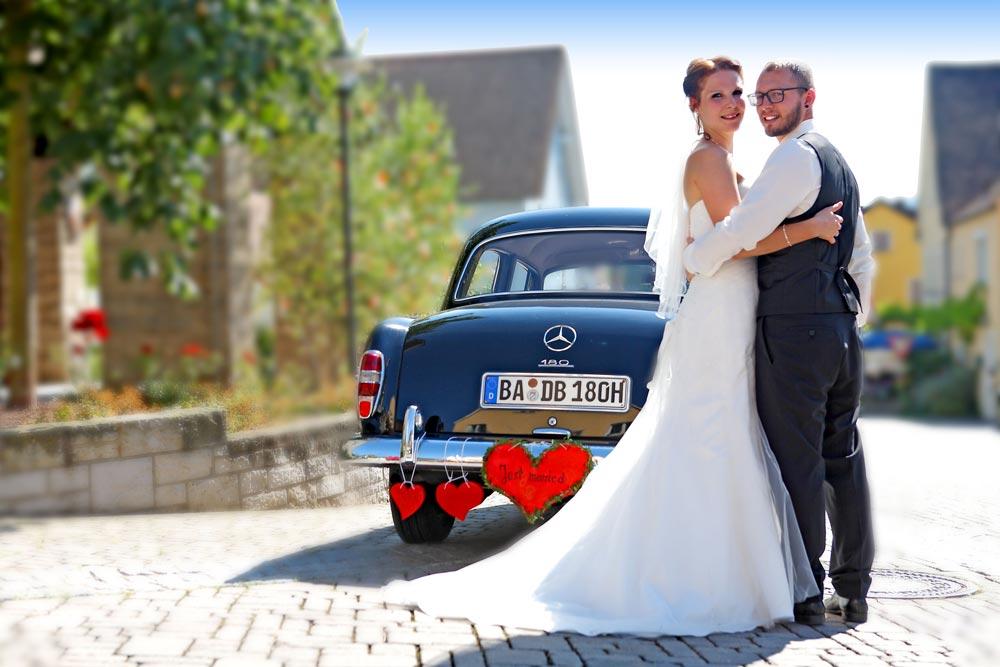 Hochzeitspaar mit Auto im Hintergrund