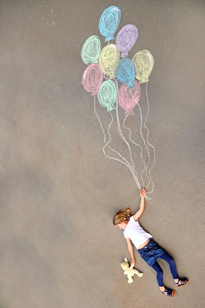 Kind mit Luftballon auf dem Boden