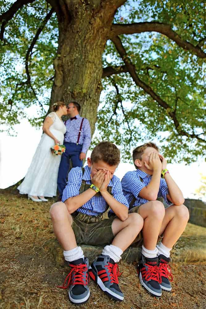 Hochzeitspaar küsst sich im Hintergrund, Kinder im Vordergrund schauen weg