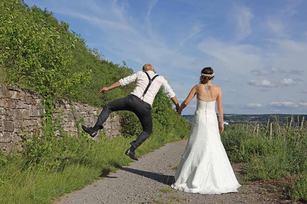 Hochzeitspaar, Hand in Hand, Bräutigam springt in die Luft