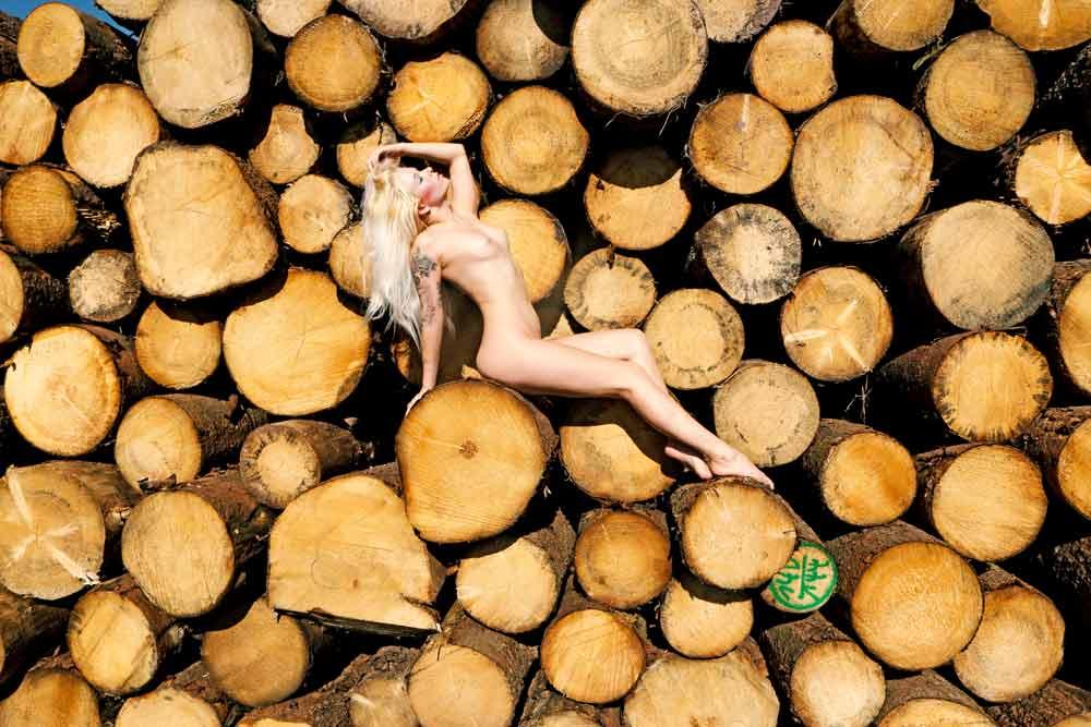 Blonde Frau Aktbild, als Hintergrund sind Holzstämme zu sehen