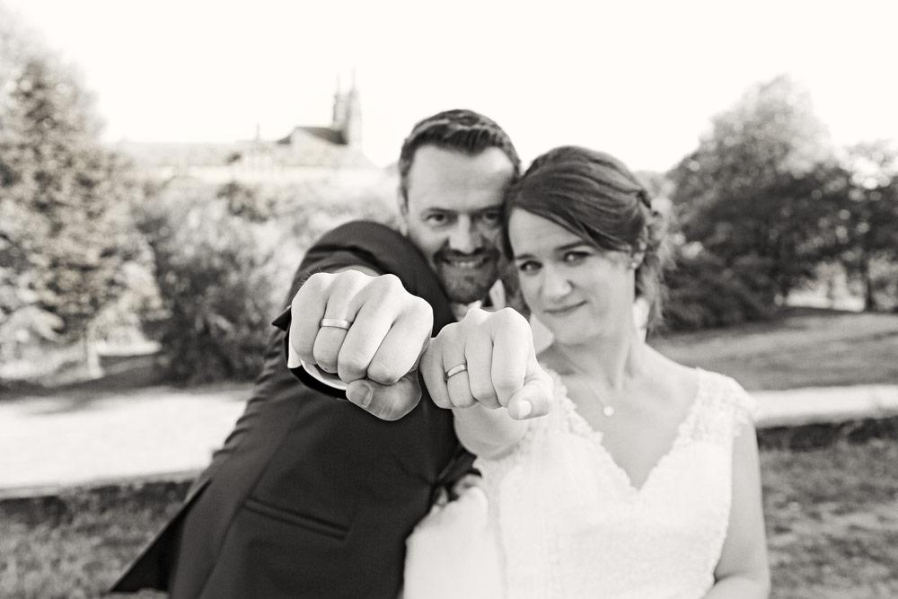 Hochzeitspaar mit Faust nach vorne, Die Fäuste mit den Ringen sind scharf. Das Hochzeitspaar im Hintergrund Unscharf