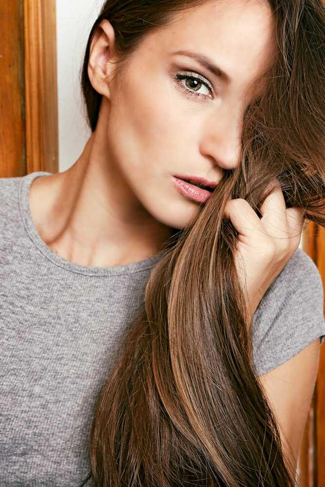 Portrait junge Frau mit braunen Haaren. das Gesicht ist zur hälfte bedeckt