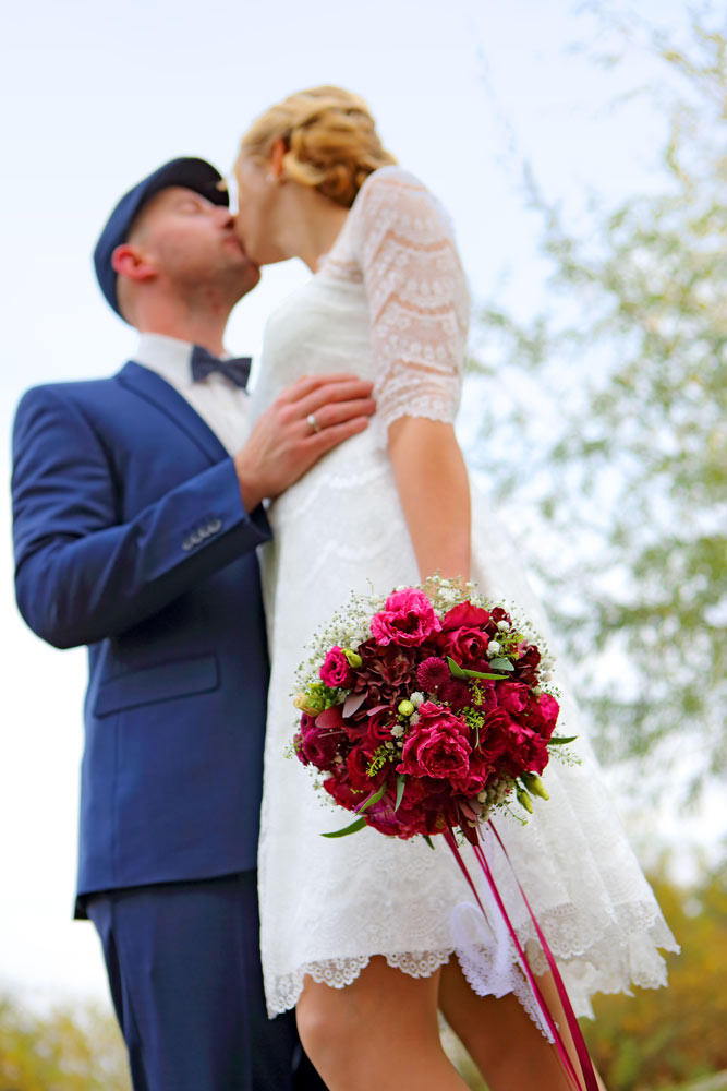 Hochzeitspaar, Strauß im Vordergrund scharf, brautpaar unscharf
