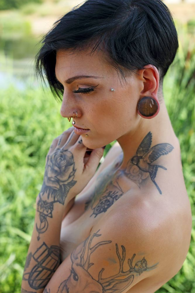 Portrait von junger Frau mit Tattoos und schwarzen kurzen Haaren