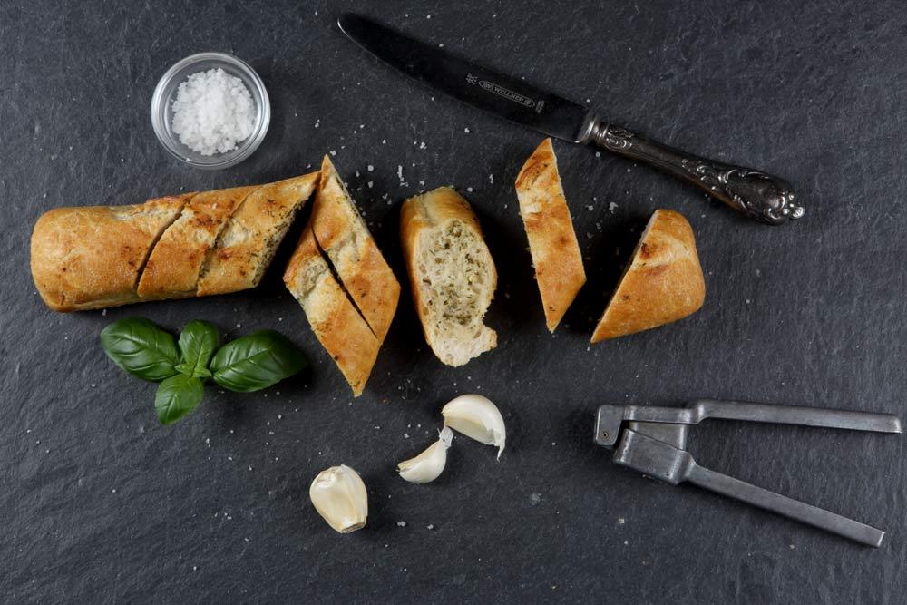Foodfotografie Baguette, von oben fotografiert, Messer, Knoblauch, Knoblauchpresse, Salz, Basilikumblätter