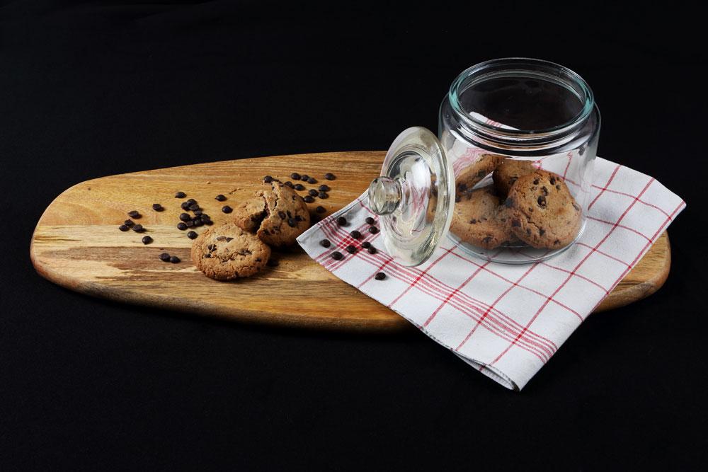 Foodfotografie, Kekse auf einem Holzbrett, rest im offenen Glas das auf einem Geschirrtuch steht, schwarzer Hintergrund