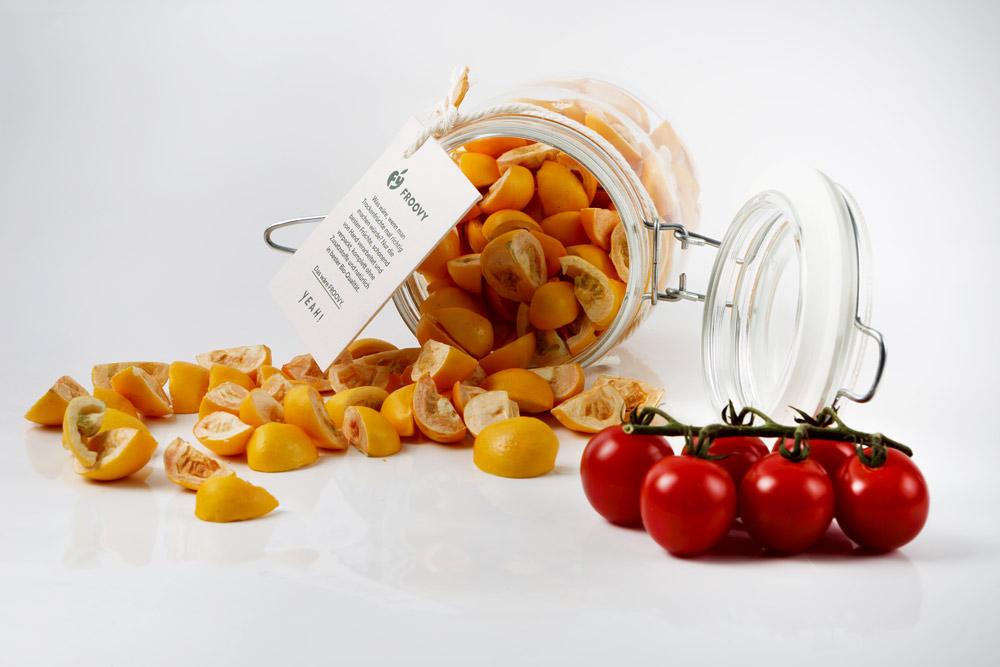 Trockenfrüchte in einem Glas umgekippt, und zerstreut auf weißen Hintergrund, im Vordergrund liegen 6 reife Tomaten am Stängel